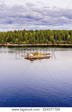 The small lighthouse on small rocky island in the archipelago near Stockholm, Sweden in Scandinavia. Bright green trees on the background. Vivid colors.