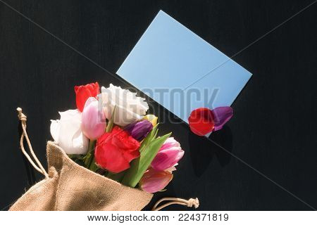 Flower bouquet and message card with petals - Colorful bouquet of diverse flowers wrapped in a jute sack and a blank blue paper note with flower petals on it, on a black background.