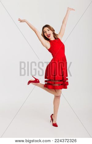 Full length portrait of a cheerful petty girl dressed in red dress posing while standing and celebrating isolated over white background