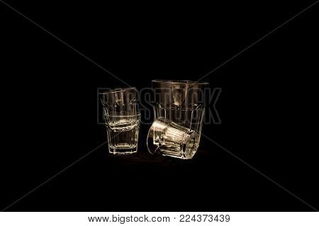 Set of empty shot glass with simple glass isolated on black background. Set glasses side by side