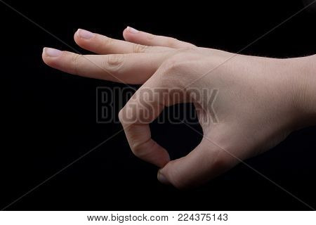 Hand gesturing sign ok okay agree on  black background