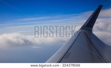 Blue sky, fluffy clouds from plane's window for backdrop. Aerial, space for text, panoramic, banner.