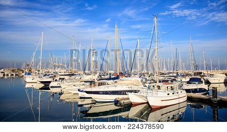 Marina at Larnaca hosts many moored boats, Cyprus. Reflection of boats, blue sky, clouds background.