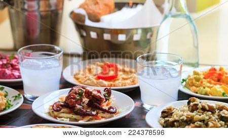 Cool ouzo in short glasses with meze, appetizers of seafood. Blurred background, close up, details