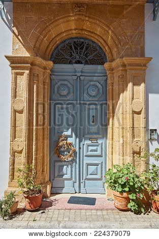 Traditional classic style old wooden medieval vintage blue painted door with knockers in Valletta, Malta.