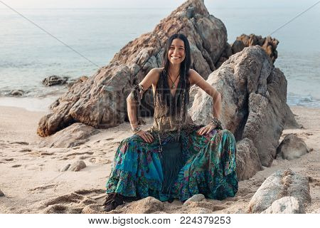 cheerful boho styled young hippie girl sitting on beach at sunset