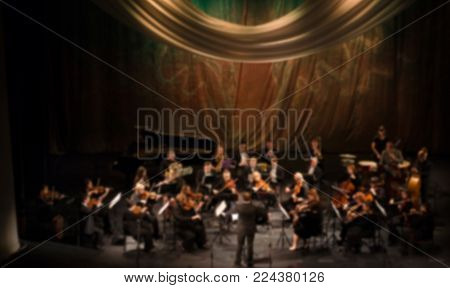 Artists symphony orchestra. abstract blurred image. Musician plays a musical instrument on the concert stage. Background for design, blur texture, actors on stage scene in concert.