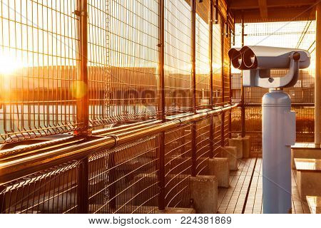 coin-operated binoculars or telescope in the morning golden glowing light for tourists to observe plane takeoffs and ladings in airport observation deck with copy space