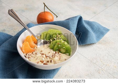 healthy breakfast from quark or curd cheese, linseed oil with omega 3 fatty acids, fresh kiwi, tangerine and nuts in a white bowl on a blue napkin, light background with copy space, selected focus, narrow depth of field