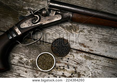 Shotgun rifle with gunpowder and many plumbeous fractions lead shot on wooden table background, top view. Hunting equipment close-up.