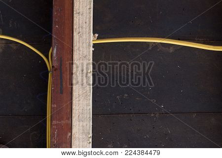 Straight view of sistering of old and new wall studs for structural support, yellow electrical wiring against construction felt, copy space, horizontal aspect