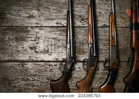 Hunting guns frame on wooden table background with copy space for text, top view. ollection of hunting rifles. Rifles, shotguns on wooden table background, hunting equipment close-up