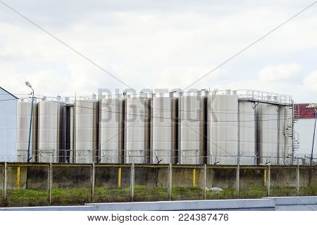 Stainless steel tanks at the winery. Winery. Wine and alcoholic beverages production.