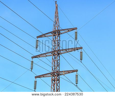 Metal support (elektroopora) of overhead power lines against a blue sky.