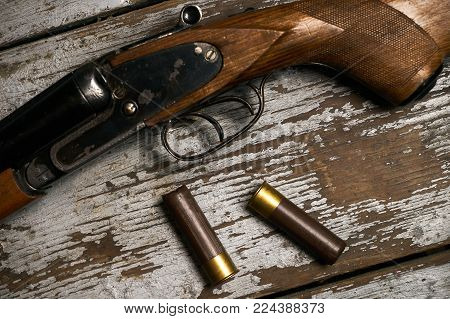Hunting rifle with cartridges lying on a wooden table. Guns with bullets close-up