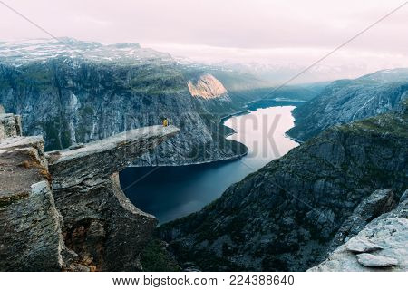 Breathtaking view of Trolltunga rock - most spectacular and famous scenic cliff in Norway. Picturesque landscape with sunset sky and clear lake