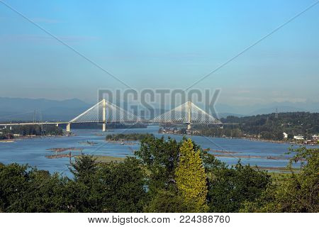 Panoramic view of the Fraser River and Port Mann Bridge against the backdrop of a mountain ridge