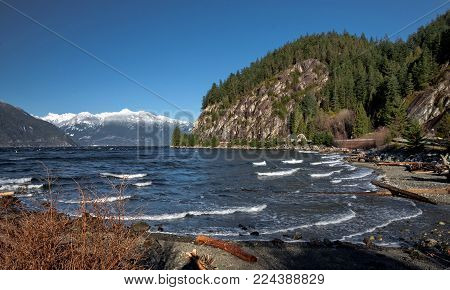 Porteau Cove Provincial Park.  Sunny spring day, sea and mountains, snow-covered mountain range on the horizon,  British Columbia.  Canada.