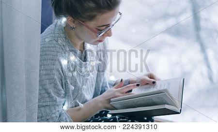 Portrait of a cute girl in glasses at the window. She is reading a book. Festive garland in the frame.