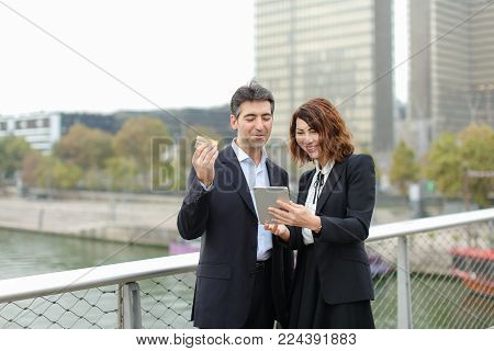 Strict dressed man and woman buy goods by credit cart in tablet. Couple walking in City center. Wife suddenly remembers about last hours of discounts in fashion shop and told husband that should make purchases right now.