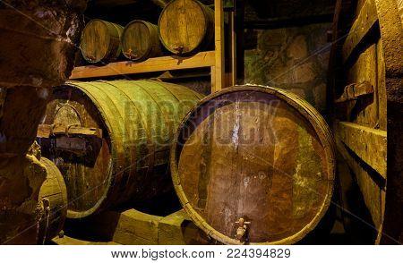 Old wine barrels in dark cellar close-up