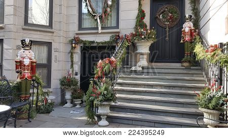 Christmas Holiday Nutcracker decorations and green wreaths adorn front steps in winter