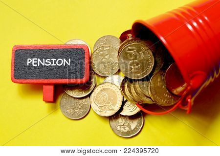 Top view of red pile with coins and blackboard written with 'PENSION' on yellow background. Business and finance theme.