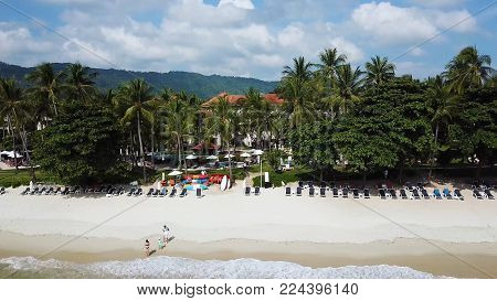 Top View of Paradise Beach. Beautiful tropical island with sand beach, palm trees. Aerial view of tropical beach on the island. Tropical landscape: beach with palm trees. Seascape: Ocean, sky, sea.