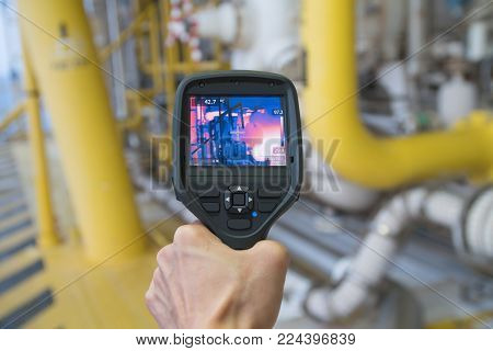 Production operator survey hot spot at hazardous area at offshore oil and gas remote platform to fine any abnormal condition of gas booster compressor by using thermo scan gun.