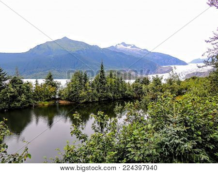Mendenhall Glacier Juneau Alaska From Trail With Lake, Forest And Mountain Range
