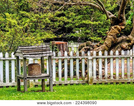 Beehive In Front Of White Picket Fence And Ancient Tree In Virginia