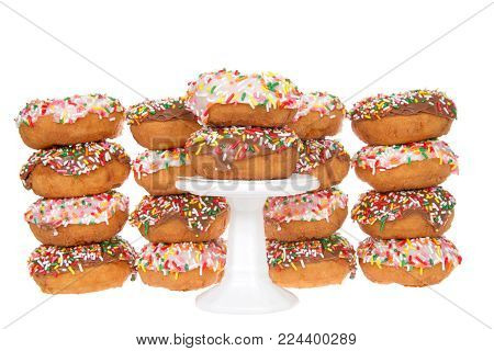 Cake donuts frosted with chocolate and vanilla frosting, rainbow candy sprinkles, stacked behind a small white pedestal with two donuts stack on top.
