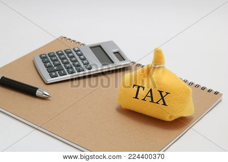Money bag, caluculator, and notebook on white background. Tax concept.