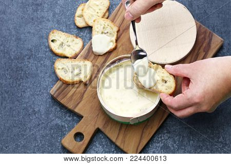 french vacherin mont d'or, soft cheese with washed rind, scooping with a spoon