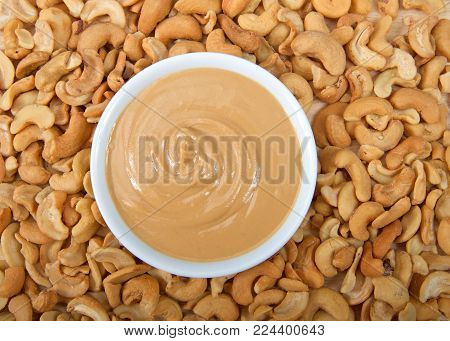 Cashew butter spread on bread on a white plate surrounded by cashew nuts. Cashews are a good source of plant protein, contain no cholesterol and are low in saturated fat.