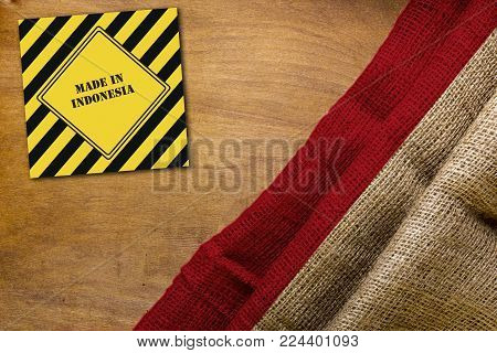 White red flag of Indonesia on a wooden background with sign made in Indonesia.