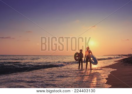 Turkey, Alanya - August 22, 2017: Two young girls walk along sea beach at sunset behind them. Summer vacation at the sea. A company of teenagers is bathing in sea with inflatable circles. Summer vacation at sea concept
