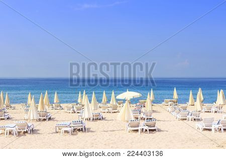 Sun beds and umbrellas on resort beach against blue sea and clear sky on bright sunny day. Beach holiday concept. Summer vacation. Tropical beach and relax