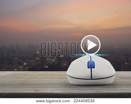 Play button with wireless computer mouse on wooden table over blur of cityscape on warm light sundown, Business music online concept