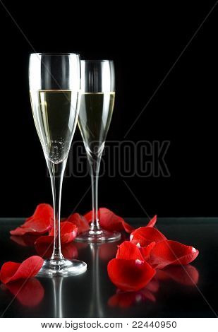 champagne glasses with petals of rose isolated on black background