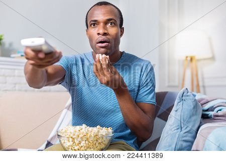 So thrilling. Nice astonished handsome man eating popcorn and being involved in the movie while watching TV