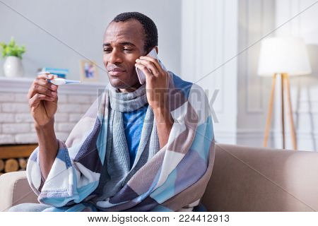Serious illness. Unhappy serious ill man looking at the thermometer and calling to the hospital while having a fever