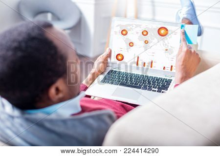 Statistic data. Handsome intelligent nice man holding a laptop and looking at the laptop screen while looking at the statistics