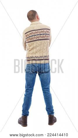 Back view of man in jeans. Standing young guy. Rear view people collection.  backside view of person.  Isolated over white background. The man in a warm sweater looks thoughtfully upward.