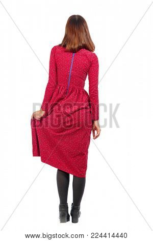 back view of standing young beautiful  woman.  girl  watching. Rear view people collection.  backside view of person.  A woman in an old-fashioned red dress keeps the dress