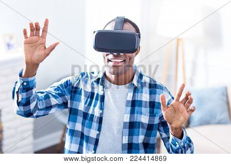 So realistic. Joyful delighted positive man wearing 3d glasses and smiling while enjoying his virtual reality experience