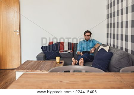 Young man lying down on his living room sofa at home browsing online with a digital tablet