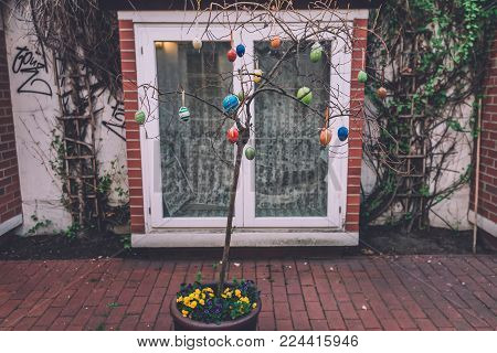 April, 9th, 2017 - Potsdam, Brandenburg, Germany. Traditional festive Easter tree pot decorated with eggs and flowers during Easter celebration in Potsdam.