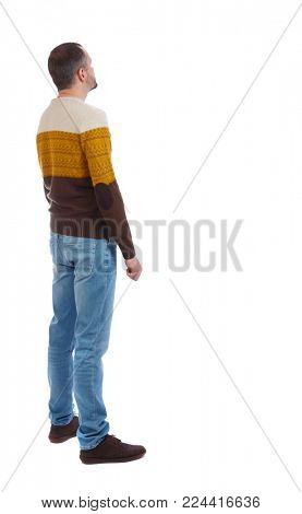 Back view of man in jeans. Standing young guy. Rear view people collection.  backside view of person.  Isolated over white background. A man in a warm sweater looks surprised upward
