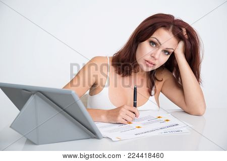Tired financial expert working with papers and looking at camera. Exhausted young businesswoman overworking in office. Fatigue concept